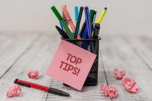 Top tips post-it note on pens on a table