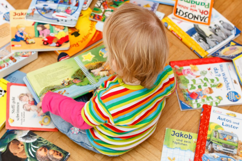 Toddler sat on wooden floor surrounded by colourful picture books.