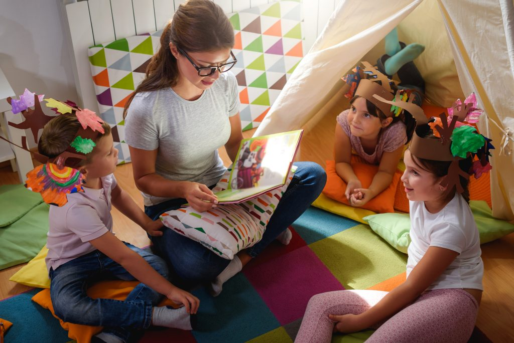 Early years practitioner reading to children on floor.