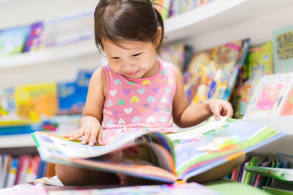Female toddler smiling at and reading a colourful book.