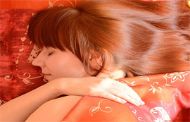 Woman asleep with red duvet.