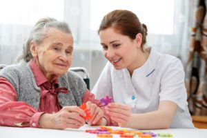 Effective communication skills. Old woman putting together a jigsaw with her carer