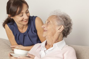 Care assistant duties. Woman giving a cup of tea to an elderly lady