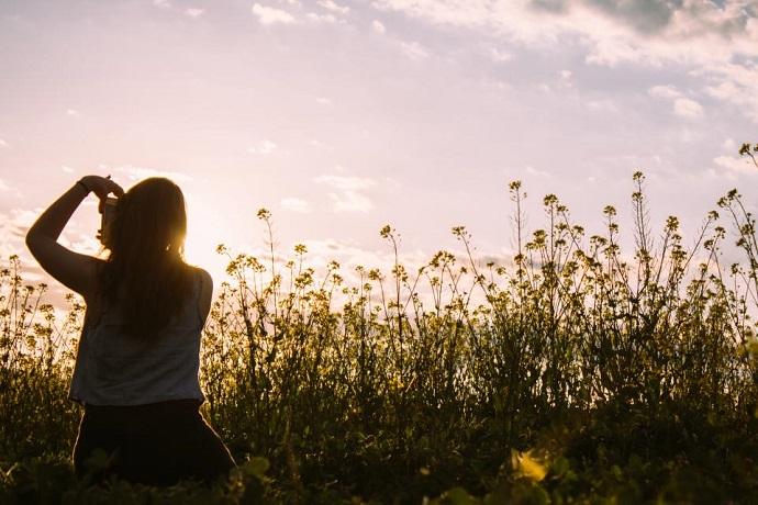 Start working in a creative job. Woman taking photo in a field
