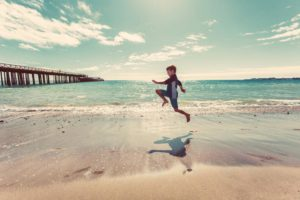 Child development. Boy jumping on a beach