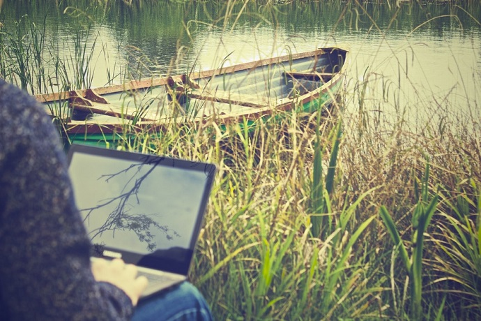 Study space. Using a laptop by a river