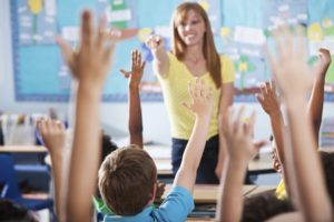 The role of a teaching assistant. Children with their hands up in a classroom