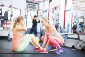 How to become a personal trainer. Two women working out in a gym