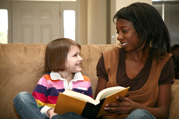 woman reading to a 5 year old girl at home.