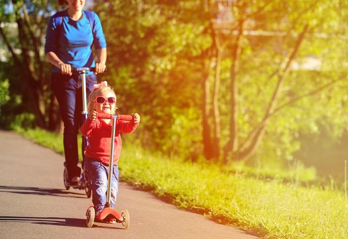 mother and cute little daughter on scooters in nature