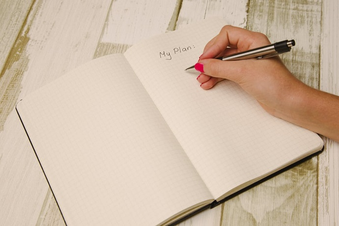 New Year's resolutions. Writing a plan in a notebook