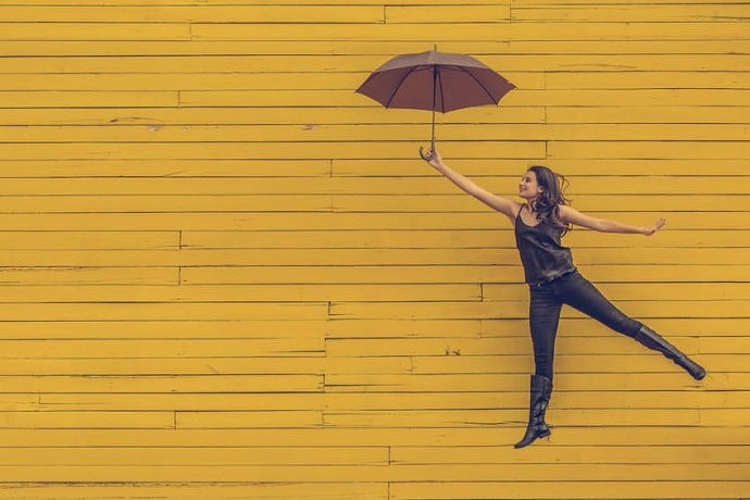 Blue Monday. Woman jumping with an umbrella against a yellow background