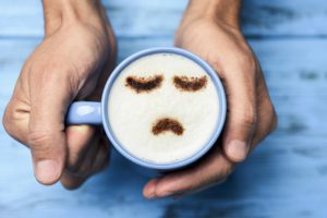 high-angle shot of a young caucasian man with a blue cup of cappuccino with a sad face drawn with cocoa powder on the milk foam, on a blue Monday on a rustic table