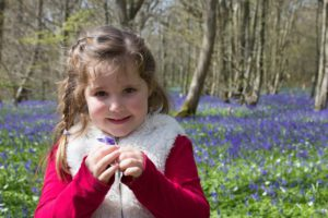 A girl picks flowers on a day out with a professional who has the qualifications to work with autistic children