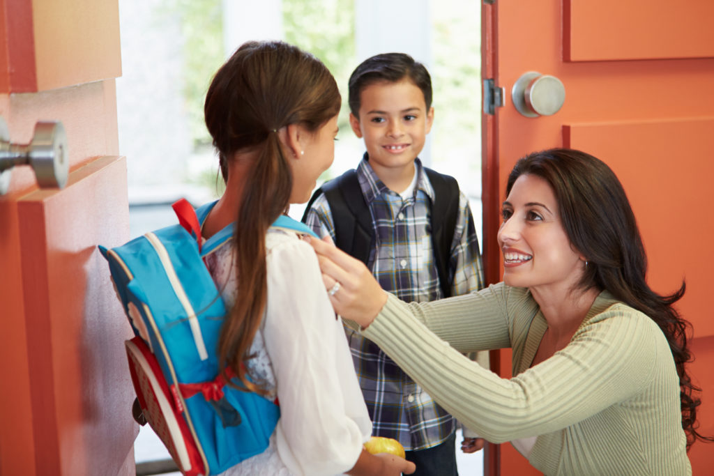 Teaching assistant preparing child to leave school