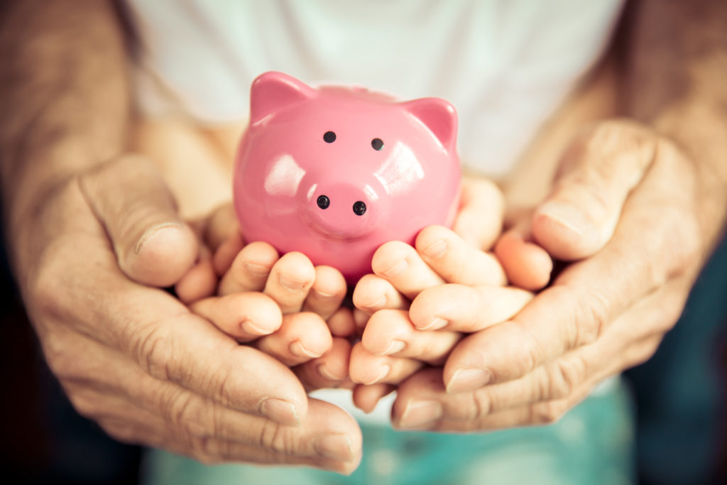 Family holding piggybank in hands after loan is paid off