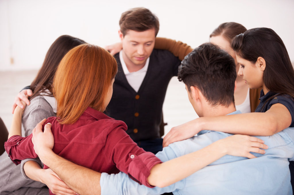 Group of people sitting in circle and supporting each other