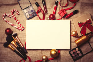 Cosmetics and Christmas gifts on jute background