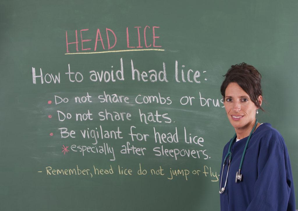 School nurse teaching about head lice on chalkboard of classroom after nursing courses