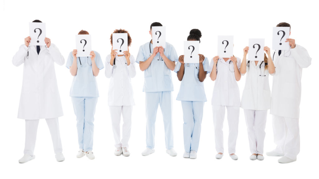 Group Of Multiracial Doctors Hiding Behind Question Mark Sign Over White Background