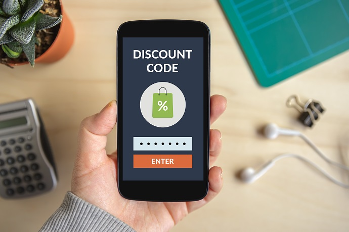 Hand holding smart phone with discount code concept on screen.