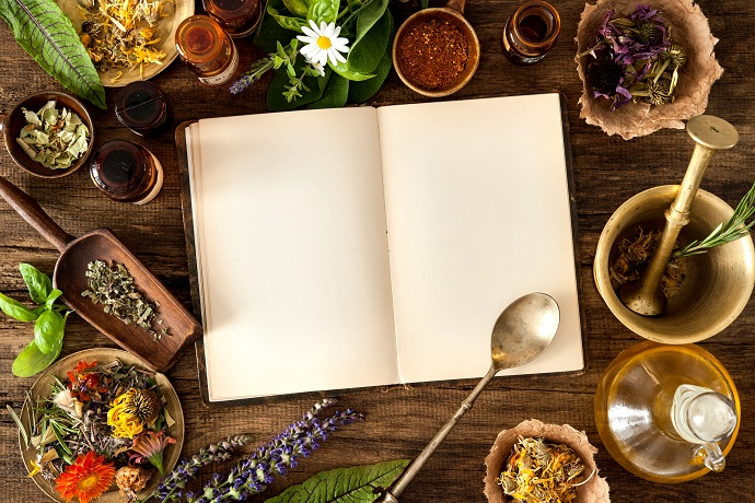 herbal remedies book on table with herbs