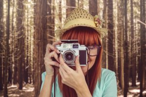 Portrait of a smiling hipster woman holding retro camera hobby