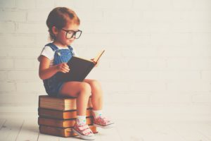 happy child little girl with glasses reading a books teachining assistant guided reading