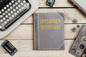 Interview Questions text on cover of old book on office desk with vintage type writer machine from 1920s and other obsolete office items.