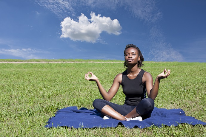 woman with a yoga hobby doing yoga in a field