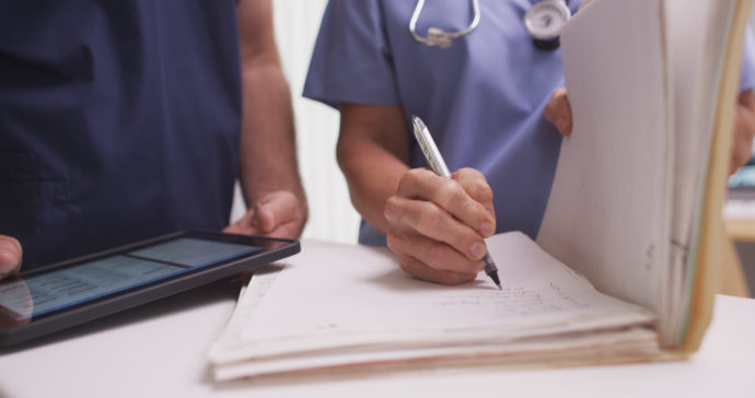 Nurse writing in patient's folder