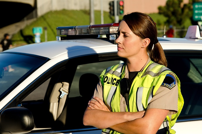 a police officer crosses her arms as she stands next to her patrol car.