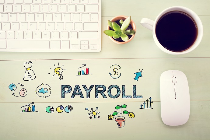 Payroll concept with workstation on a light green wooden desk