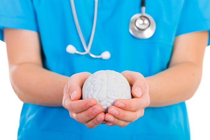 mental heath nurse holding a plastic brain in hands