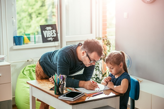 man helping child to finish homework
