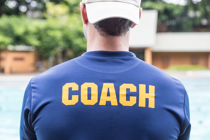 back of a sport coach's blue shirt with the yellow Coach word written on it; good background for sport or coaching theme