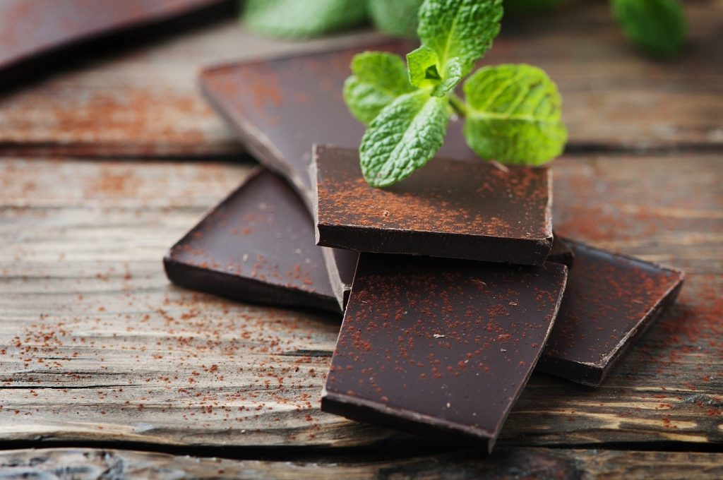 Example of chocolate superfoods: chunks of dark chocolate on a table with a sprig of mint.