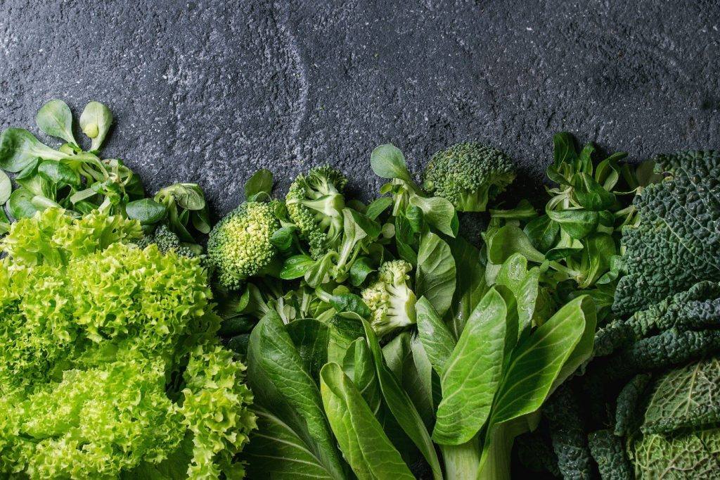 Vegetable superfoods example: leafy greens on marble background.