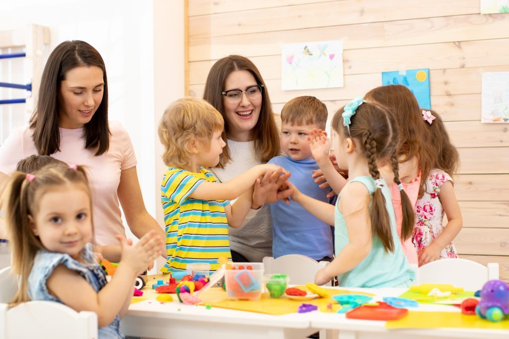 Happy teaching assistant sitting in colourful classroom with group of young children.