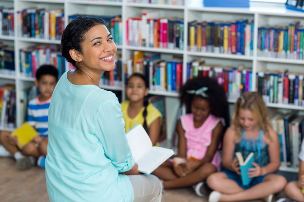 Smiling teaching assistant sat on floor for circle time with group of children.