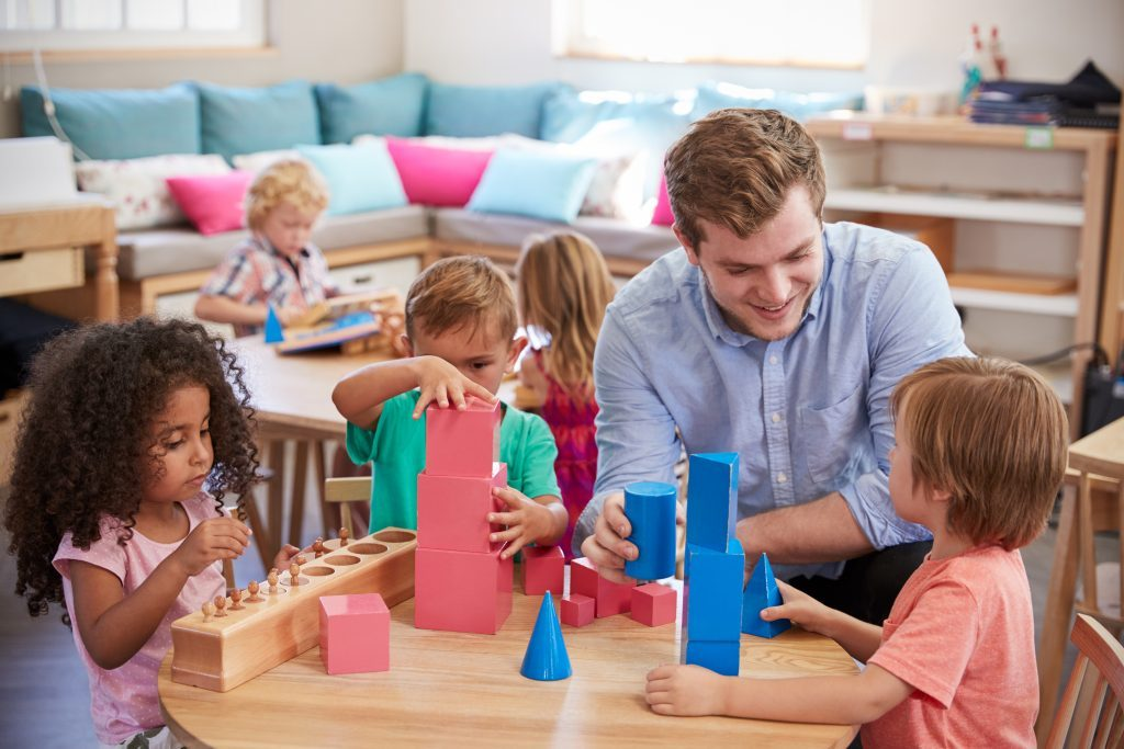 Male teaching assistant with group of children and building blocks on table.