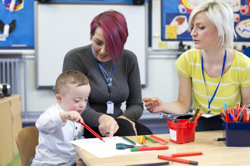 Teaching assistants assisting small boy with special educational needs.