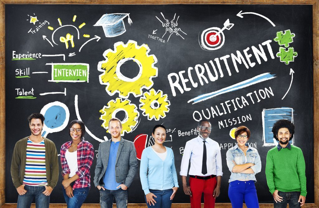 People in front of a board with 'recruitment' written on it. Teaching assistant recruitment process concept.