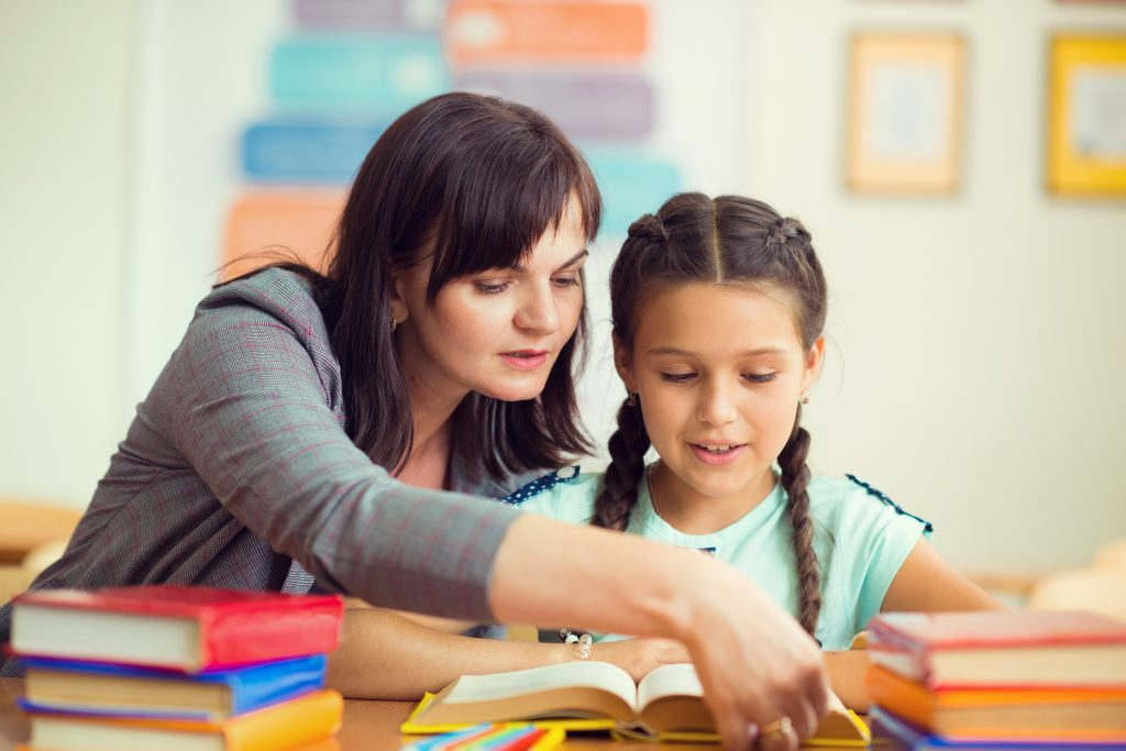 Teaching assistant helping young girl with her reading.