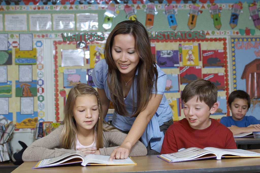Teaching assistant with two pupils in classroom, pointing to a book.