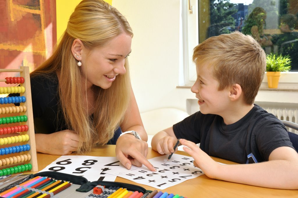 Teaching assistant sat at table with student and helping him with maths.