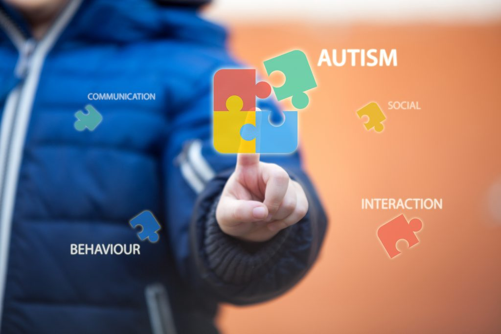 Child connecting autism (learning disability) awareness puzzle by pressing icons on digital virtual screen.