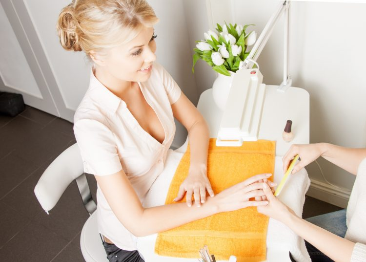 Happy client having their nails manicured in salon.