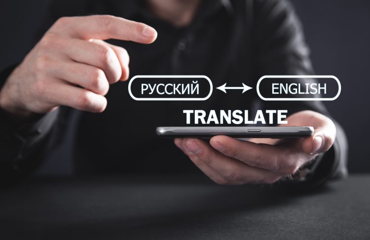 Man holding smartphone with translation concept from Russian to English.
