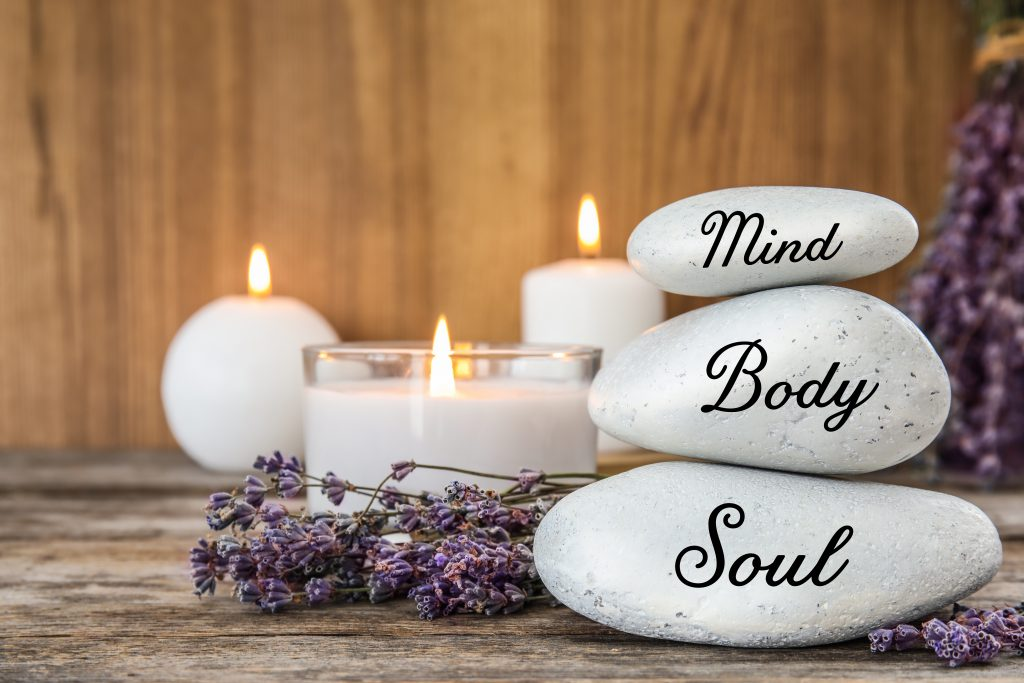 3 stones on spa table with lavender and candles. Stones have 'mind', 'body' and 'soul' written on them to demonstrate principles of holistic therapy.
